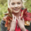 Young woman with autumn leaves — Stockfoto