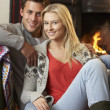 Young couple sitting by open fire — Stock Photo #11885546