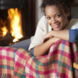 Young woman sitting by open fire — Stock Photo