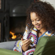 Young woman sitting by fire with phone - Stock Photo