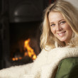 Young woman sitting by open fire - Stock Photo