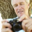 Senior man with camera — Stock fotografie