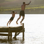 ung man med barn hoppa till vatten — Stockfoto