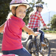 Stock Photo: Little girl on country bike ride with mom