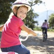 Little girl on country bike ride with mom — ストック写真
