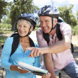Senior couple with map on country bike ride — Stock Photo