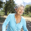 Senior woman on country bike ride — Stock Photo