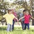 Parents playing with children in country - Stock Photo