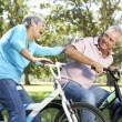 Senior couple playing on children's bikes — Stockfoto