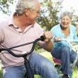 Senior couple playing on children's bikes — Stock Photo #11885946