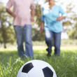 Senior couple playing football — Stock fotografie