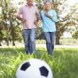 Senior couple playing football — Stok fotoğraf