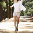 Woman running along country lane - Stock Photo