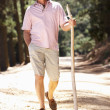 Senior man on country walk - Stock Photo