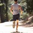 Young man running along country lane — Stock Photo