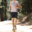 Young man running along country lane — Stock Photo #11885981