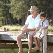 Senior man fishing with grandson — Stock Photo