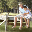 Senior man fishing with grandson - Stock Photo