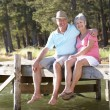 Senior couple sitting by lake — Stock Photo