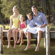 Young family sitting by lake — Stock Photo