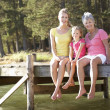 Mother,daughter and grandmother sitting by lake - 