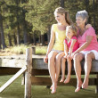 Mother,daughter and grandmother sitting by lake — Stock Photo