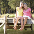 Mother and adult daughter sitting by lake — Stock Photo