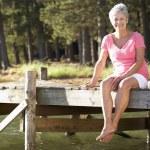 Senior woman sitting by lake — Stock Photo #11886097