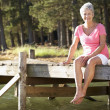 Stock Photo: Senior womsitting by lake