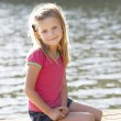 Young girl sitting by lake — Foto Stock