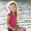 Young girl sitting by lake — Stock fotografie