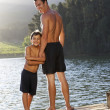 Father and son standing on jetty - Stock Photo