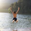Young boy jumping into lake - Stockfoto