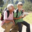 Senior man reading map with grandson on country walk — Stock Photo