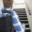 Man in wheelchair at foot of stairs — Stock Photo