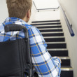Man in wheelchair at foot of stairs - Stock Photo