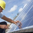 Man installing solar panels - Stock Photo