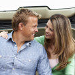 Couple outdoors with car - Stockfoto