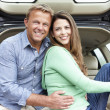 Couple outdoors with car - Stock Photo