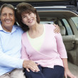 Senior Hispanic couple outdoors with car — Stock Photo #11887384