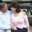 Senior Hispanic couple outdoors with car — Stock Photo