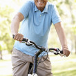 Senior Hispanic man riding bike — Stock Photo