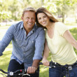 Couple riding bikes in park — Stock fotografie