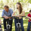 Family riding bikes in park — Stock Photo