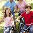 Hispanic family riding bikes in park - Stock Photo