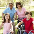 Hispanic family riding bikes in park — Stock Photo #11887562