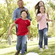 Family playing football in park — Stock Photo