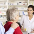 American pharmacist dispensing to senior couple — Stock Photo #11887747