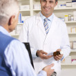American pharmacist with senior man in pharmacy — Stock Photo #11887786