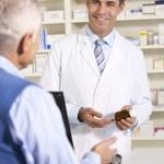 American pharmacist with senior man in pharmacy — Stock Photo